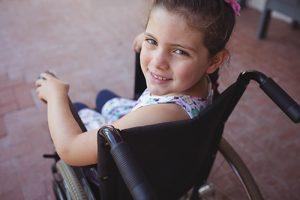 High angle portrait of schoolgirl sitting on wheelchair at school