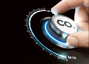 Man turning a carbon dioxyde knob to reduce emissions. CO2 reduction or removal concept. Composite image between a hand photography and a 3D background.